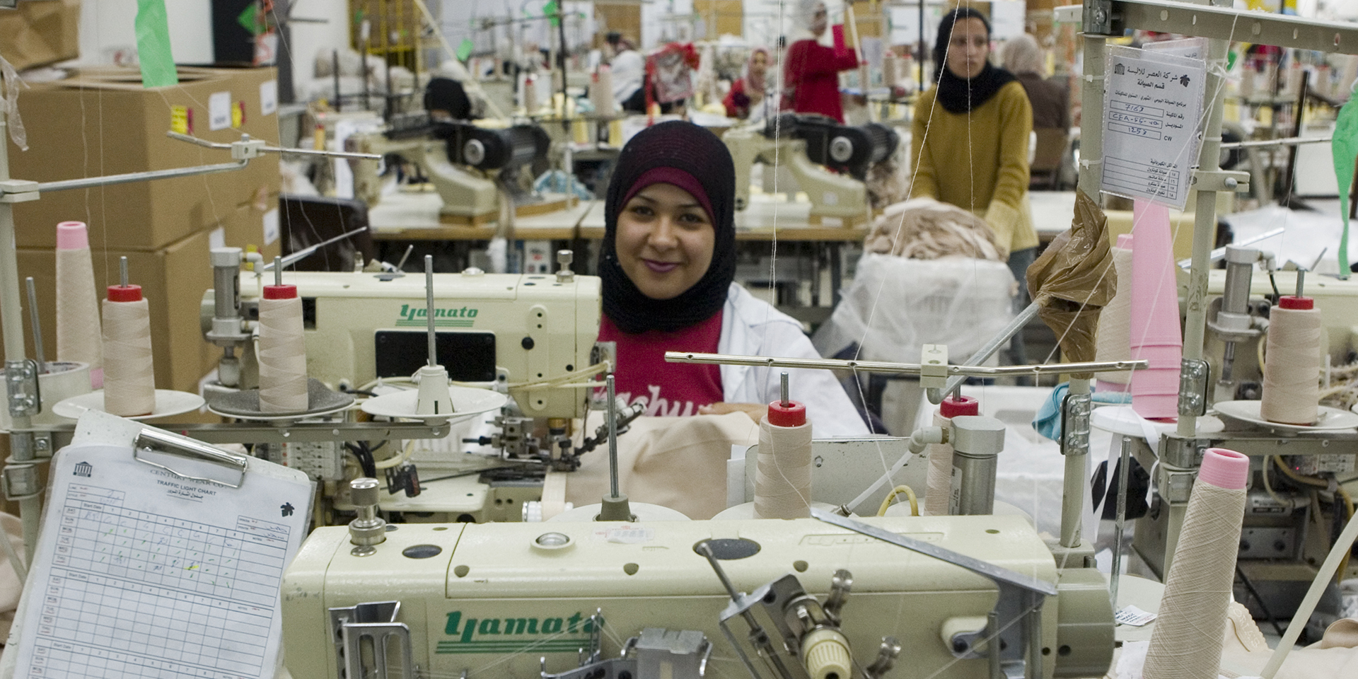 A woman smiles from behind a sewing machine at Century Wear Factory in Irbid, Jordan