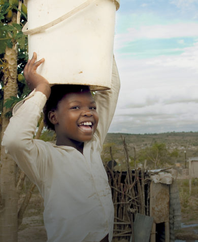Smiling girl in South Africa carrying water