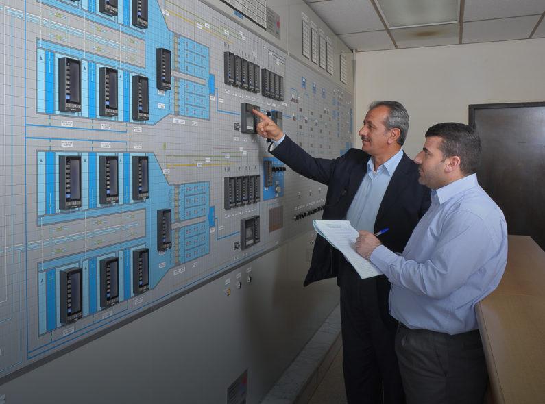 Two men examine a control panel in Jordan.