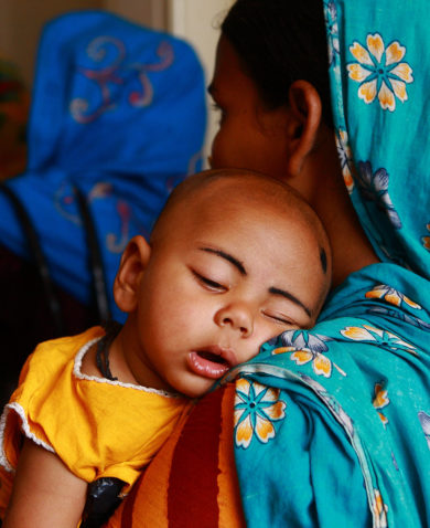A baby sleeps on his mother's shoulder