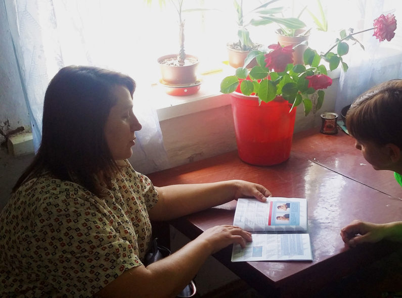 A health worker speaks with a TB patient in the patient's home.