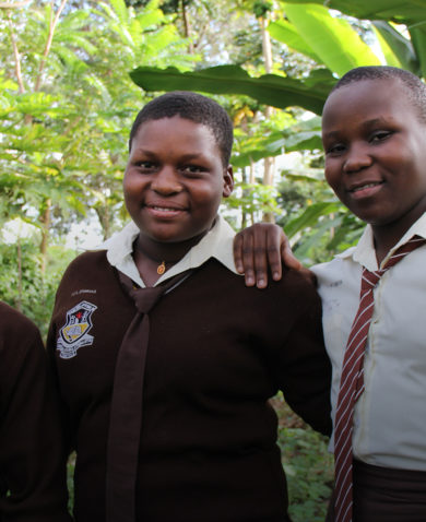 Three female students stand in their school's garden.