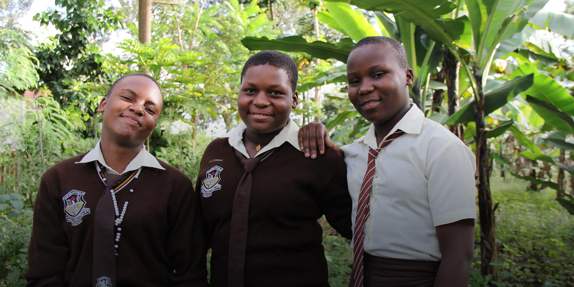 Three female students stand in their school's garden.