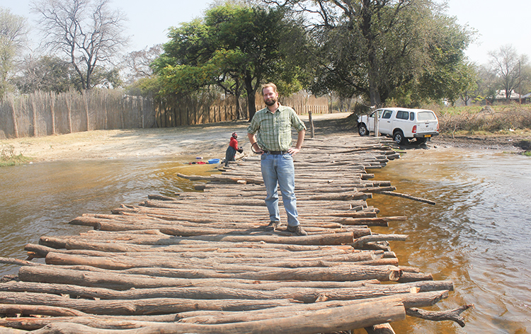 Brian App standing on a river crossing comprised of logs