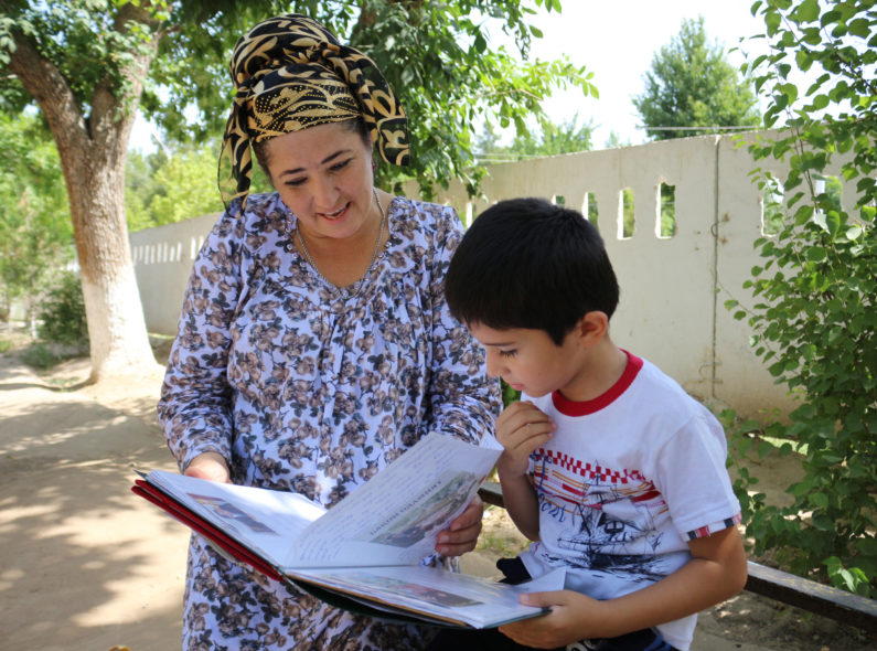 Manzura and her son Vohidjon read together.