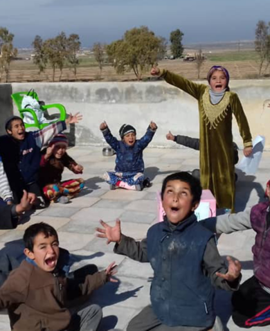 Children sitting in a circle shout happily
