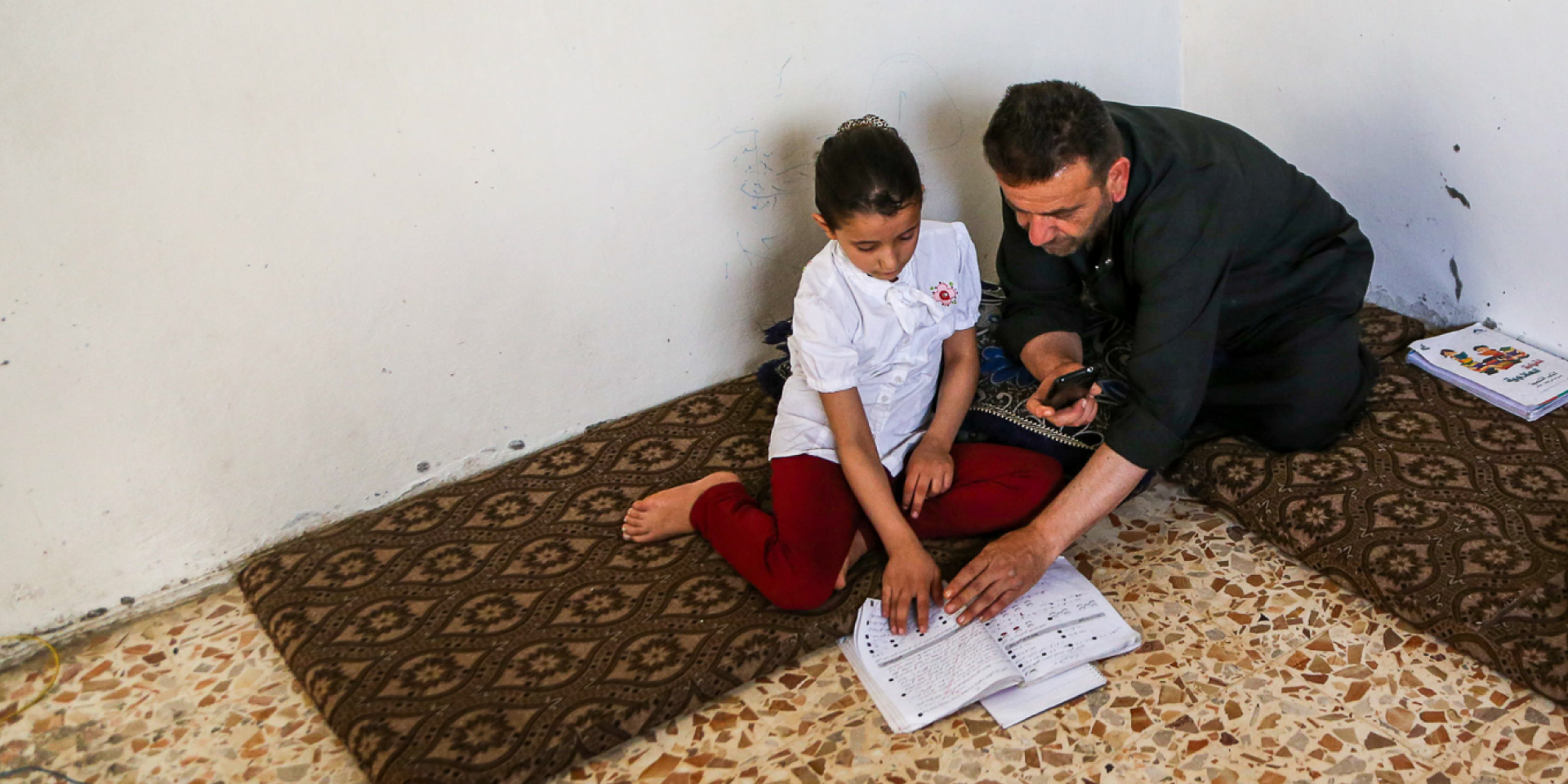 In Northwestern Syria, Rama and her father, Fadi, use his smartphone to watch a virtual Arabic class on WhatsApp, supplemented by textbooks.