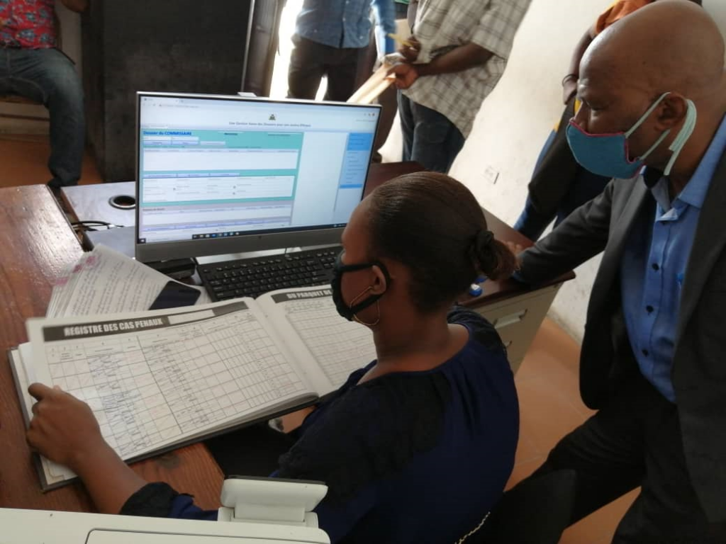 Wildor Faustin from the CMIS Task Force assisting a clerk in the court of Mirebalais to enter data in the CMIS