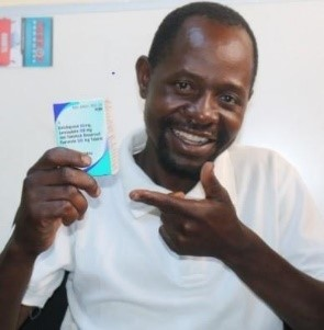 Harrison Nzima happily holds his antiretroviral treatment, TLD