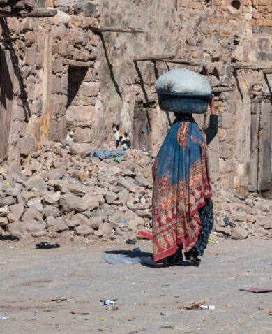 A woman with a basket on her head walks down a road in Sanaa, Yemen.