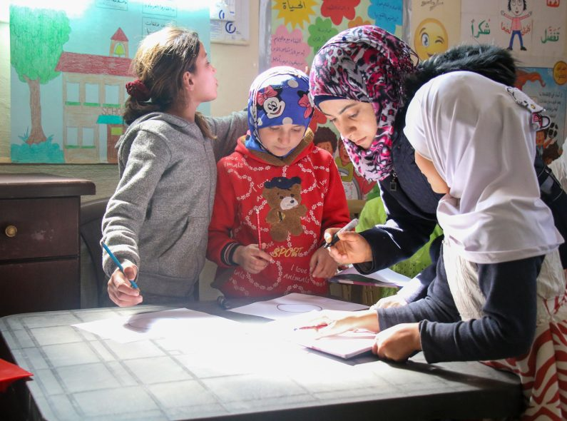 A teacher in Syria supports her students to draw pictures.