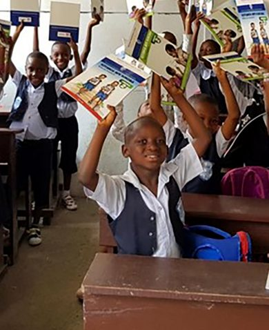 A group of children lift textbooks in the air happily