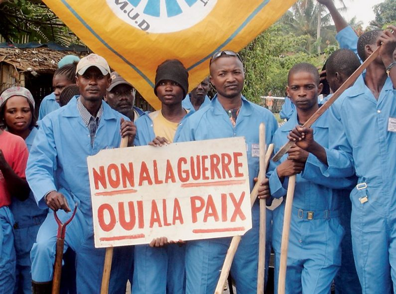 Congolese men dressed in blue stand holding a sign asking for peace