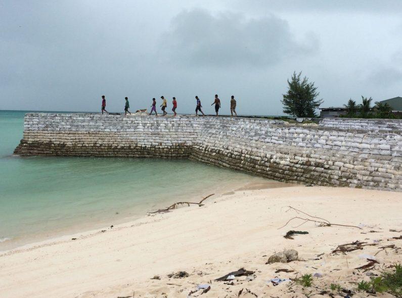 A group of young people walk along a sea wall in Tarawa, Kiribati.