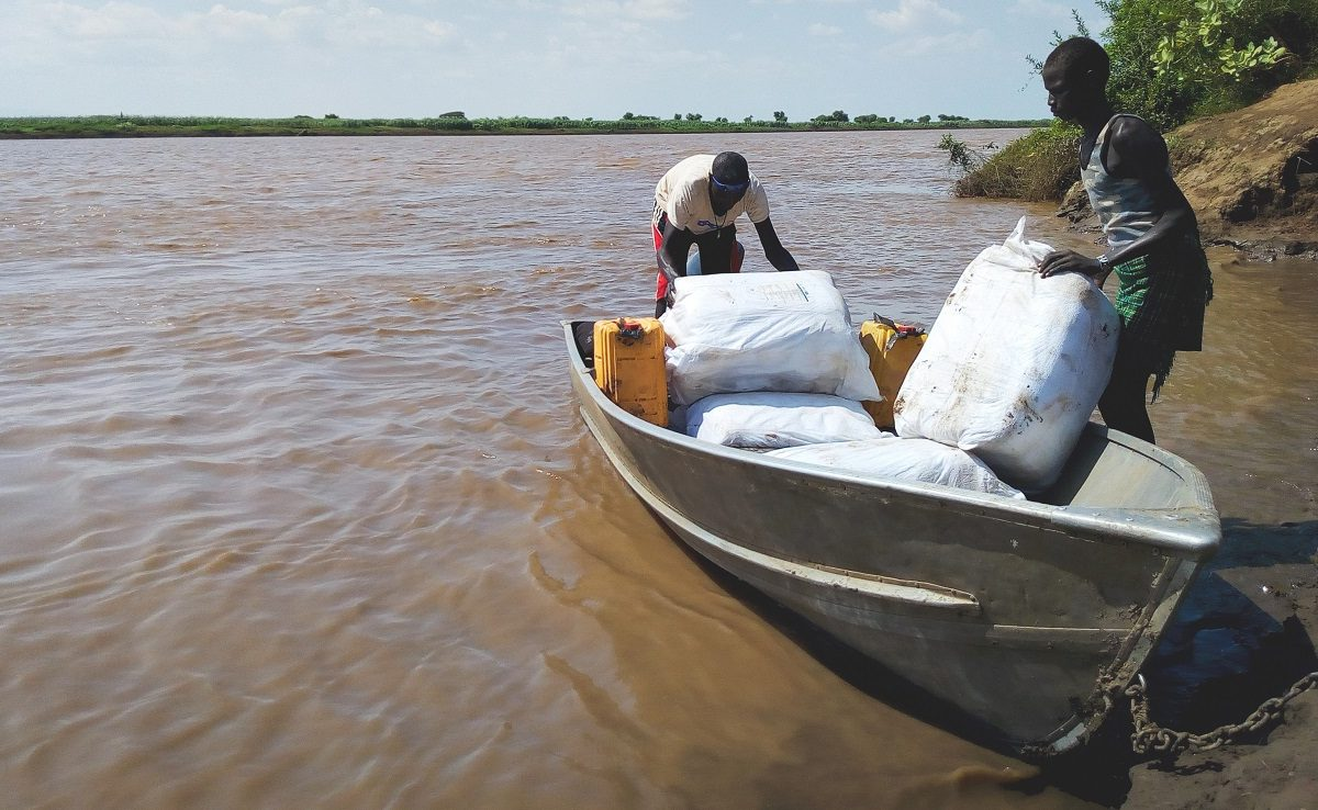 Men load a boat with bundles of mosquito nets