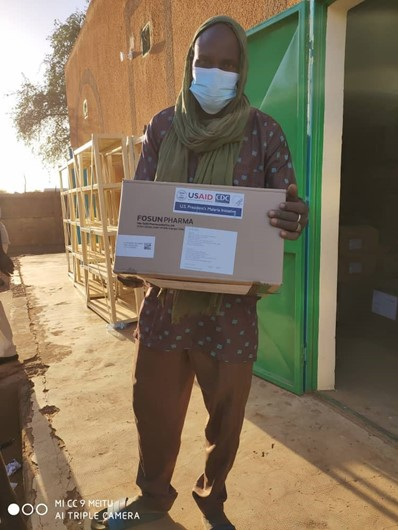 A man holding a box of health commodities that have been delivered to AB484_Bourgami.
