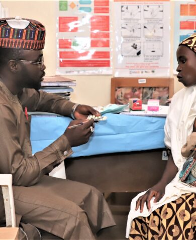 Man provides anti-malarial drugs to a woman holding a baby in Nigeria.